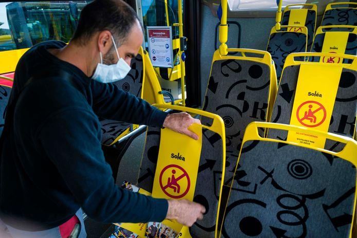 Employé masqué marquant les distances à respecter dans un bus, en mai, à Mulhouse