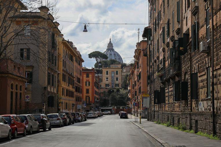 De Sint-Pietersbasiliek achter een lege straat in Rome, Italië. Beeld Getty