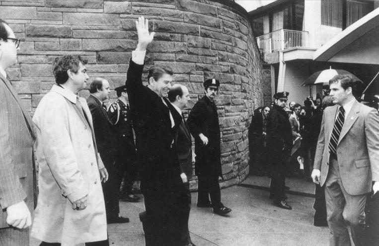 James Brady (derde van links) en Reagan (zwaaiend, midden) vlak voor de aanslag op president Reagan op 30 maart 1981. Beeld AP