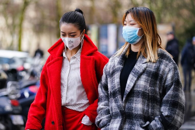 Twee gasten van de modeweek in Parijs dragen mondkapjes.  Beeld Getty Images