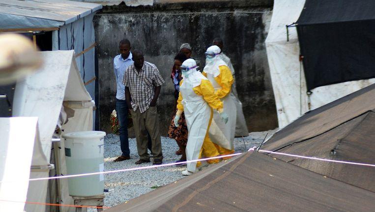 Medewerkers van een gezondheidsdienst in Sierra Leone dragen beschermende kleding op de plek waar het Donka-ziekenhuis patiënten met ebola heeft opgevangen.