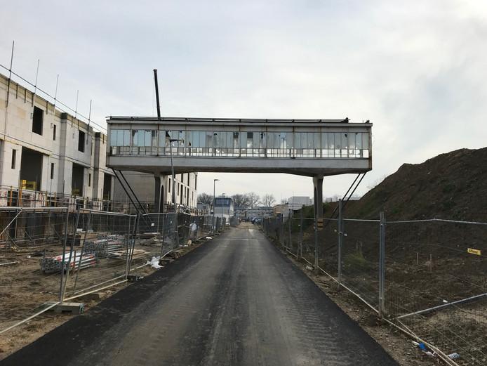 Een foto van de huidige situatie rond de loopbrug op Strijp-R in Eindhoven, met links de andere nieuwbouw in aanbouw. Rechts komt het Bruggebouw te staan.
