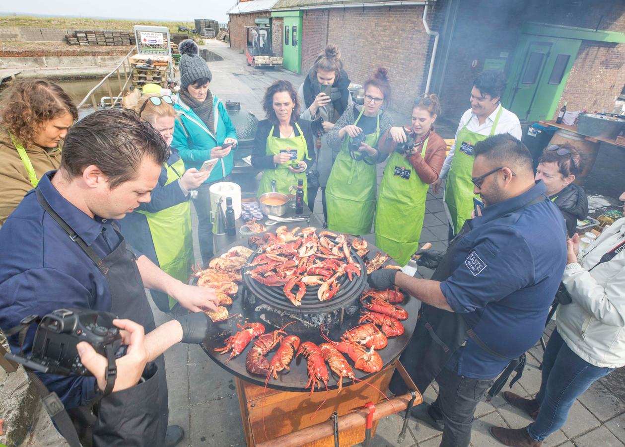 Bastiaan Sinke van 'Taste Culinair' en Suranga Neels leggen nog wat kreeften op de bakplaat. Alles wordt vastgelegd door de foodbloggers.