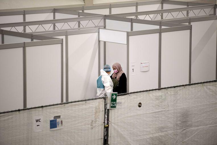 Een bezoekster met luchtwegklachten komt bij een arts. In topsportcentrum De Koog is een tijdelijke huisartsenpost ingericht om patiënten met griep- en eventueel coronaverschijnselen op te kunnen vangen. Beeld ANP