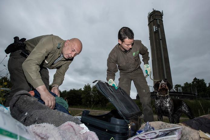 Philip Oprel (l), groene BOA, en boswachter Erik de Jonge onderzoeken samen met de hond achtergelaten spullen aan de bosrand. Brabants Landschap huurt handhaving extern in. Die club beschikt wel over een vuurwapen.