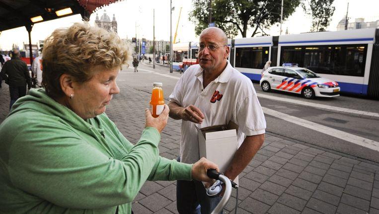 Fred Teeven deelde op de dag van de verkiezingen nog flesjes vruchtensap uit voor Amsterdam CS. Beeld anp