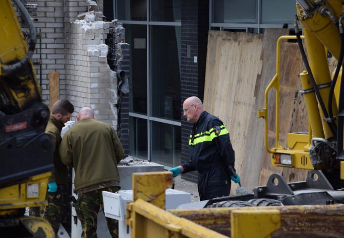 Een agent kijkt met de EOD mee terwijl ze naar achtergebleven explosieven zoeken.