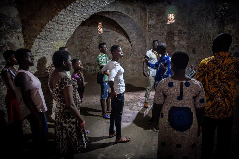 Bezoekers tijdens een rondleiding in de kerkers van fort Elmina. Beeld Sven Torfinn
