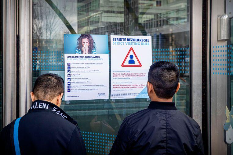 Bezoekers van het ErasmusMC in Rotterdam lezen de bezoeks- en gedragsregels. Beeld null