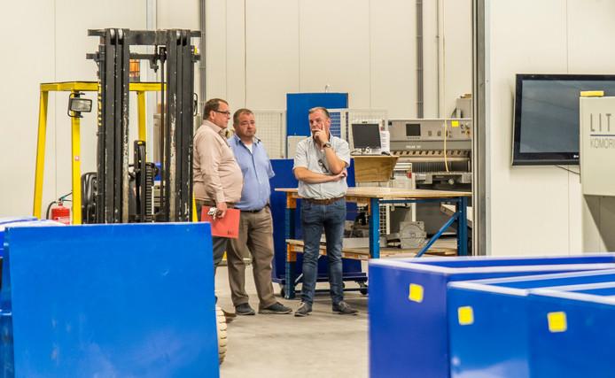 De directieleden Jaap de Leeuw (rechts)  en Hendrik-Jan van Heteren (midden) van Drukkerij Verhaag kijken gelaten toe tijdens de kijkdag.