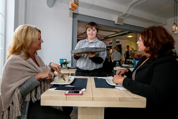Een werknemer van Brownies & Downies bedient gasten in de lunchroom. Deze zaak aan de Oostwal in Oss is het zevende filiaal van Brownies & Downies.
