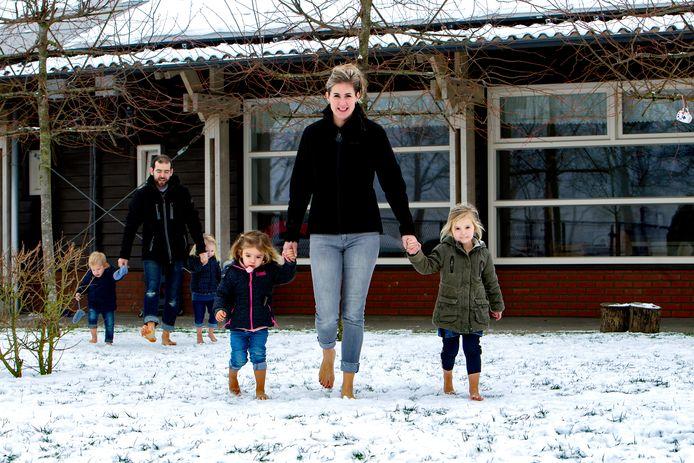 Assistent leidinggevende Angela Jacobs met peuters op blote voeten door de sneeuw.