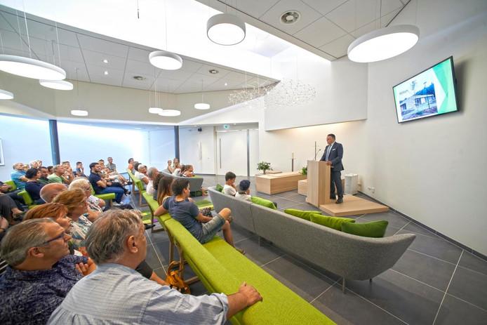 Bezoekers luisteren in de vernieuwde aula naar integratiemanager Peter Engelen.
