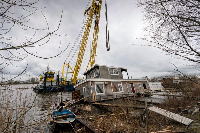 Een drijvende bok takelt woensdag deze beschadigde woonboot omhoog voor reparatie.