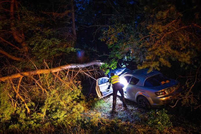Een agent bekijkt de schade aan de auto.