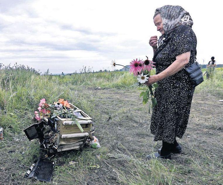 Een Oekraïense vrouw toont respect op de rampplek. Beeld epa