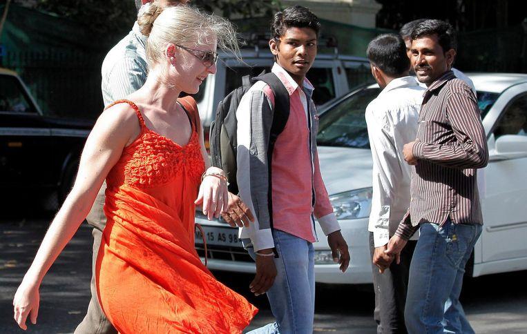 Een Westerse toeriste in een jurkje wordt in Mumbai op straat nagestaard door voorbijgangers. Beeld epa