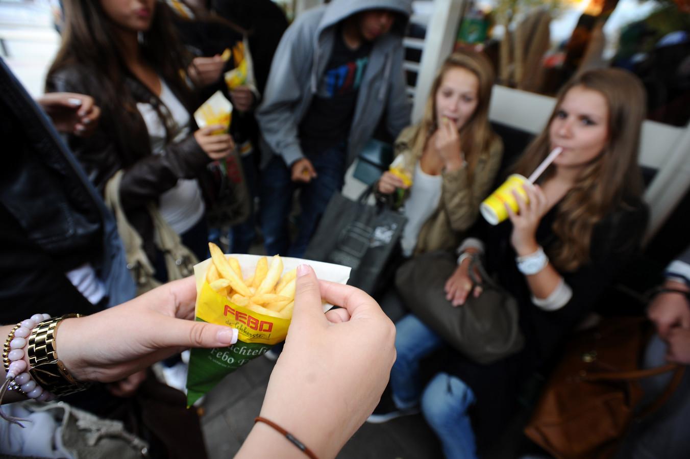 Jongeren genieten van een patatje bij de FEBO in Amsterdam.