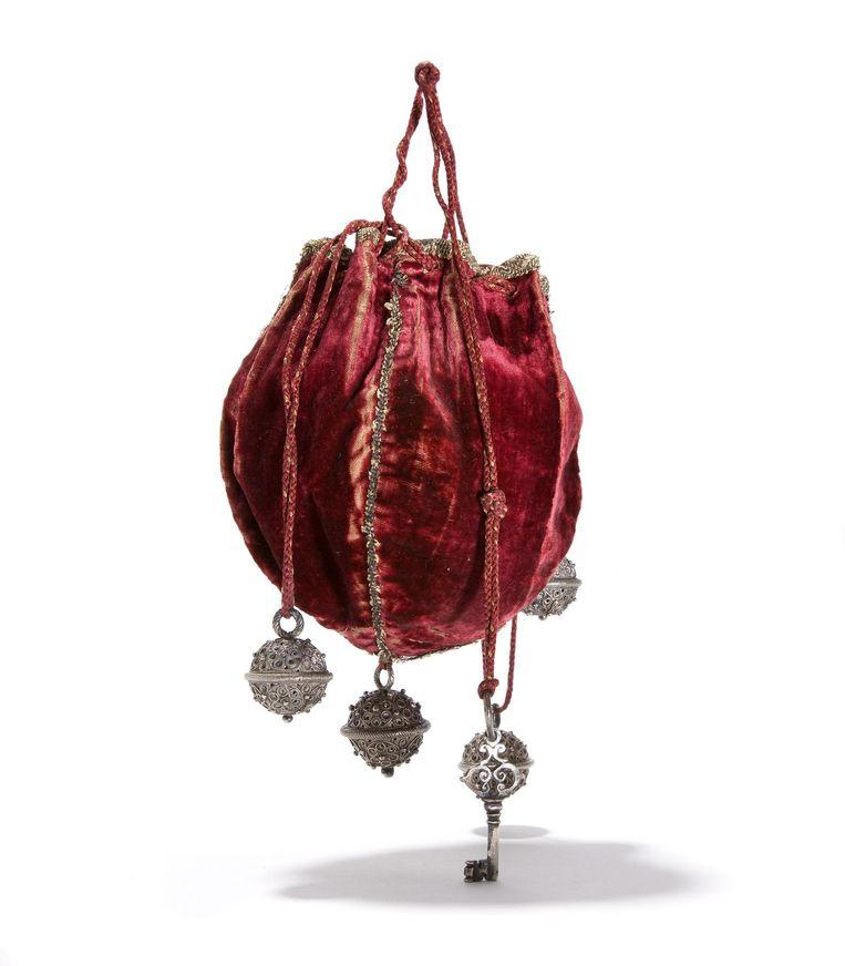 Een Nederlandse fluwelen buidel uit het begin van de Gouden Eeuw. In de zilveren balletjes konden bloemen en kruiden worden gestopt, bij wijze van parfum. Het sleuteltje is een verwijzing naar de slotvrouwen uit de middeleeuwen. Beeld Tassenmuseum Hendrikje