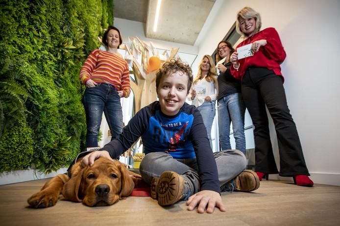 """Hessel en hulphond Bössel. Vanaf links achter hem: moeder Renée,  Rosanne Veld en Monique Heskamp van Kracht Werkt en Karin Freriksen van WISH3: """"De verzekering vergoedt niets."""""""
