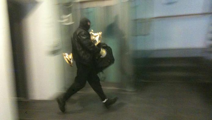 De dader loopt met de monstrans om te vluchten op de scooter.