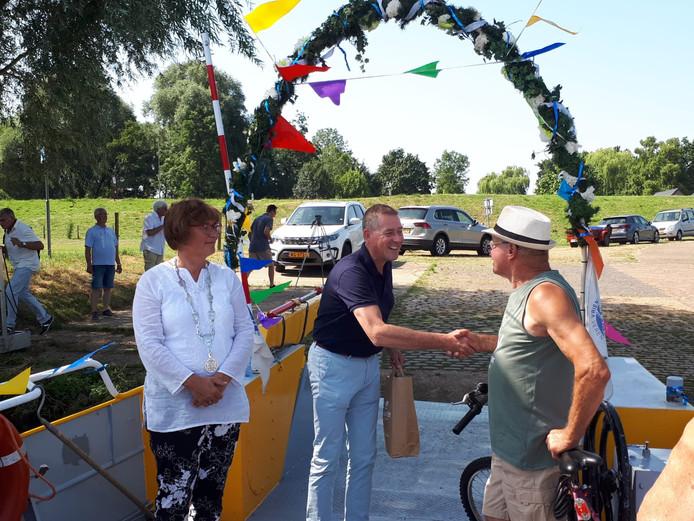 Alex Kwakernaak feliciteert Gijs van Dijk als honderdduizendste passagier van het voetveer Niftrik-Ravenstein. Burgemeester Wobine Buijs kijkt toe.
