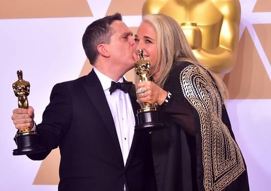 Filmmakers Lee Unkrich en Darla K. Anderson poseren met hun Oscars voor Coco.