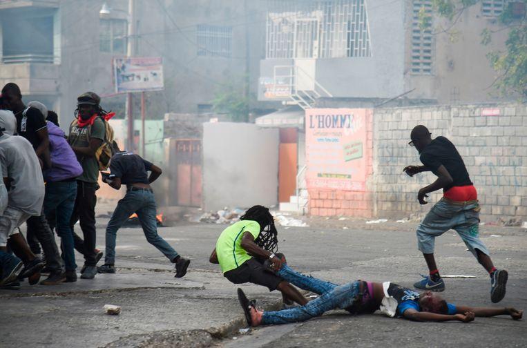 Een man valt terwijl hij het lichaam van een dode kameraad mee wil slepen tijdens protesten in de Haitiaanse hoofdstad.