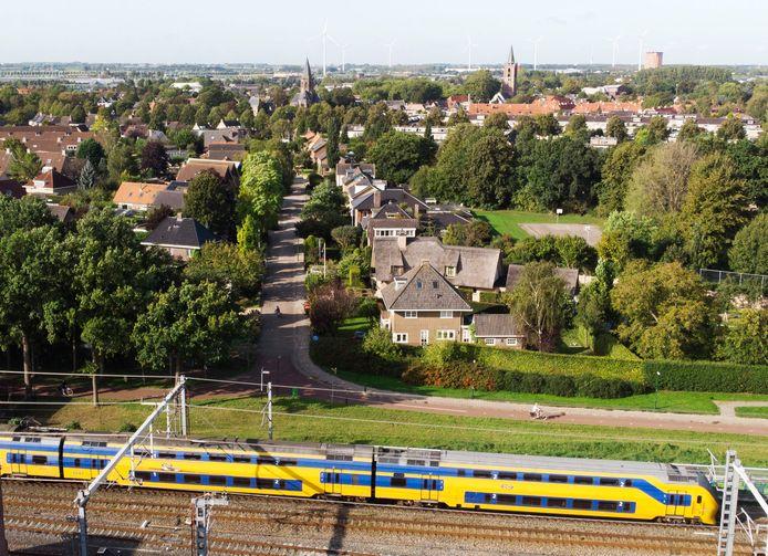 Een Intercity rijdt langs de Vlierweg in Houten, omwonenden klagen al jaren over trillingen. Op de achtergrond het Oude Dorp van Houten.