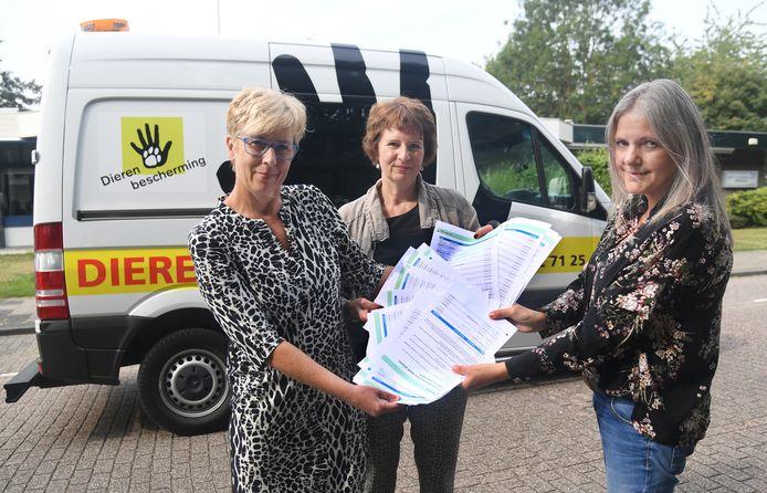Jolanda Lichtenberg (rechts) overhandigt een stapel handtekeningen aan Nita Kramer (links) en Dorien Schuurmans (midden) van de Dierenbescherming.