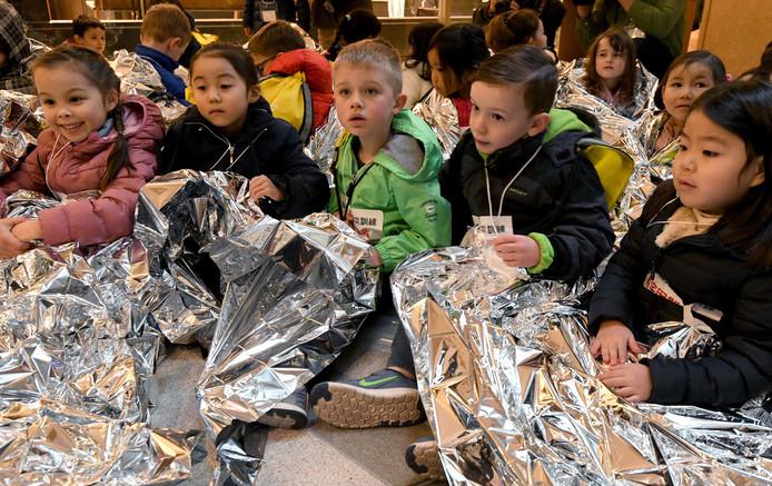 Kinderen van een internationale school in Japan zitten onder aluminium dekens om warm te blijven tijdens de jaarlijkse rampoefening in Tokio. Het is 23 jaar geleden dat Japan werd getroffen door een grote aardbeving waarbij 6.400 mensen omkwamen. Foto Toru Yamanaka