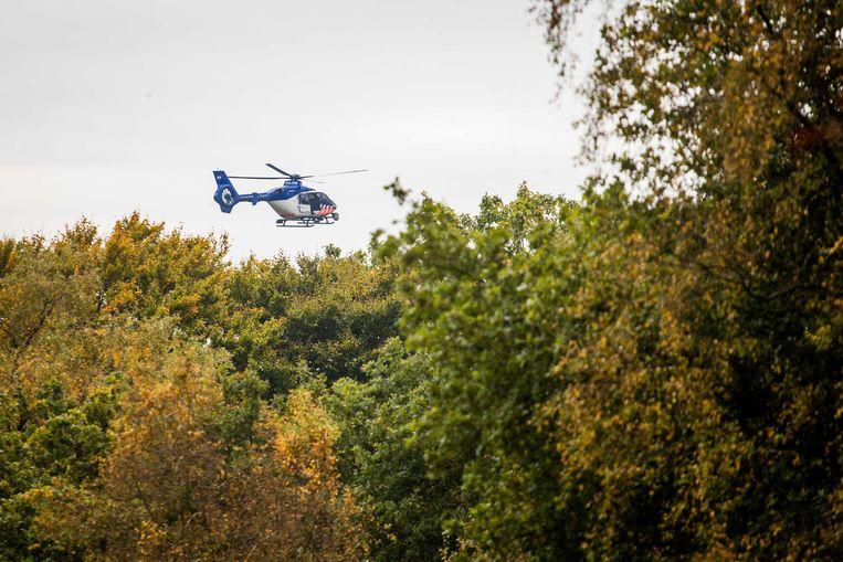 Een helikopter vliegt laag over. Om foto's van het terrein te maken, zegt de politie. Beeld ANP