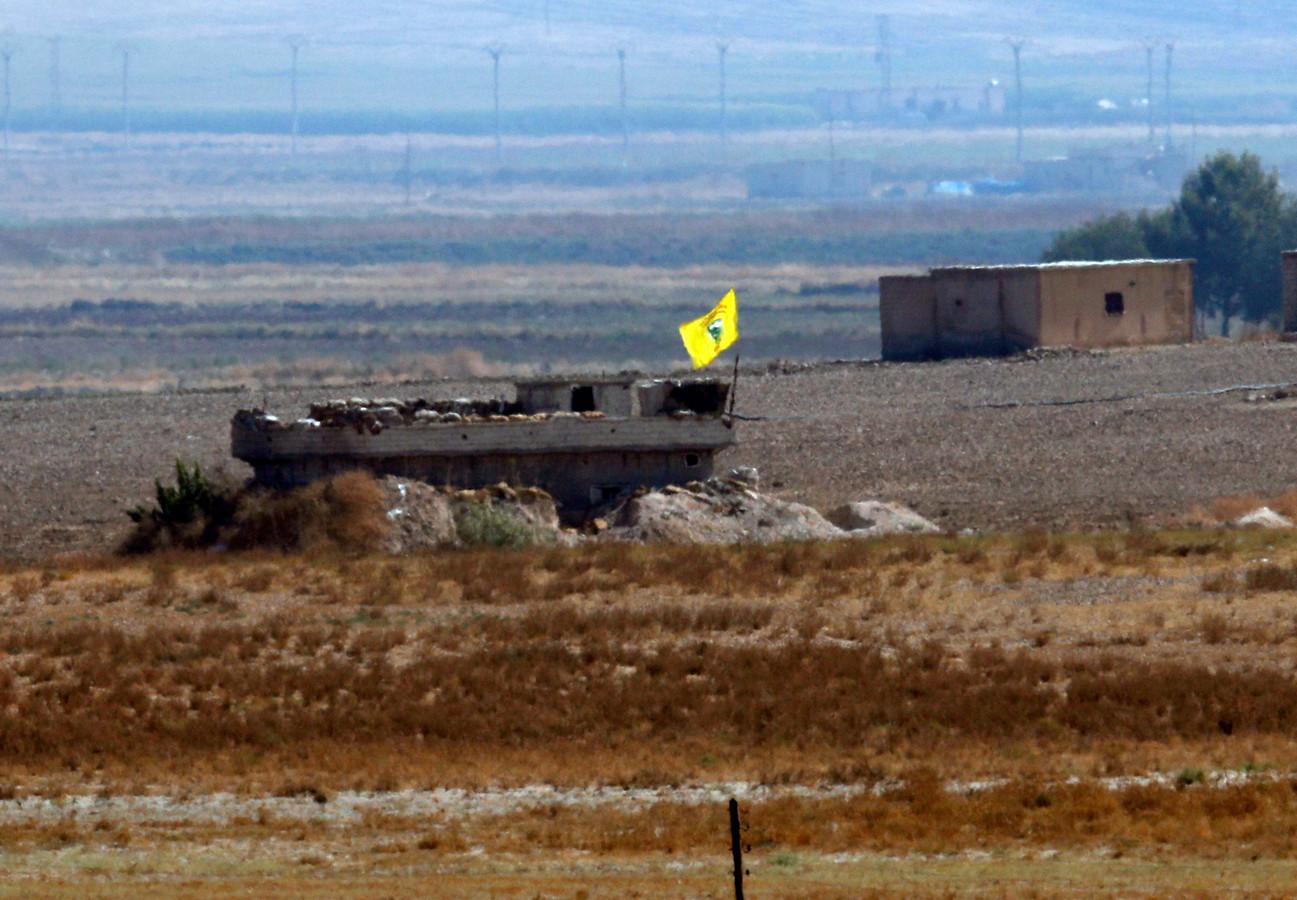 Een Koerdische YPG vlag op een verwoeste woning in Syrië.