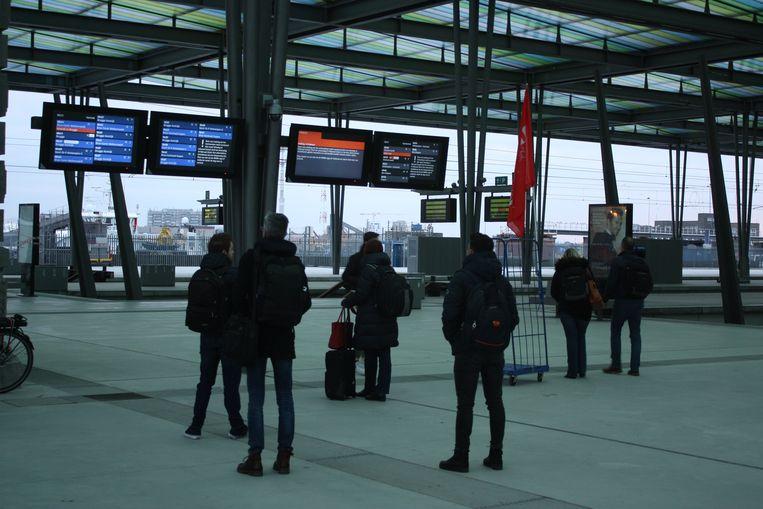 Reizigers bekijken de informatieborden in het station van Oostende om te weten te komen of ze vandaag op hun bestemming zullen geraken