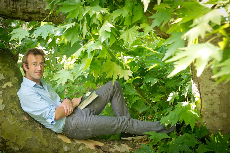 Robert Macfarlane bij een eeuwenoude plataan in de tuin van Emmanuel College in Cambridge.