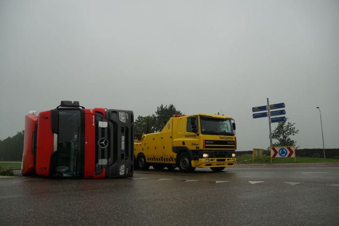 De vrachtwagen belandde op zijn kant. De chauffeur bleef ongedeerd.