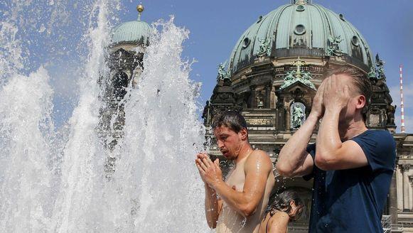 Mensen zoeken verkoeling aan een fontein bij de Dom in Berlijn.