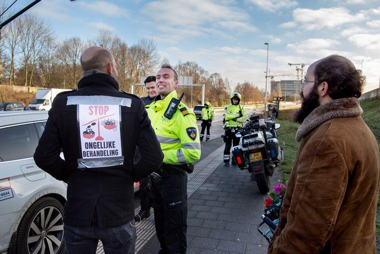 Demonstranten hebben geplastificeerde postertjes op ruggen geplakt met teksten als 'Stop ongelijke behandeling' en 'Rondje A10, le jour de gloire est arrivé!'. Beeld Pauline Marie Niks