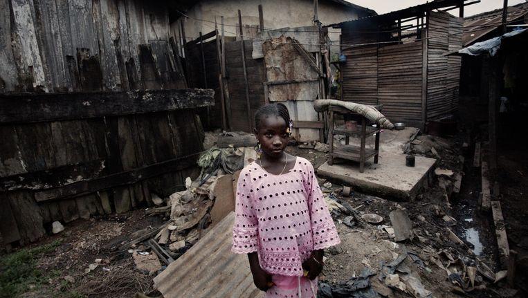 Een meisje in een sloppenwijk in San Pedro (Ivoorkust). Veel inwoners hoopten werk te krijgen in de cacaostad, maar zijn op zichzelf teruggeworpen. Beeld Daniel Rosenthal