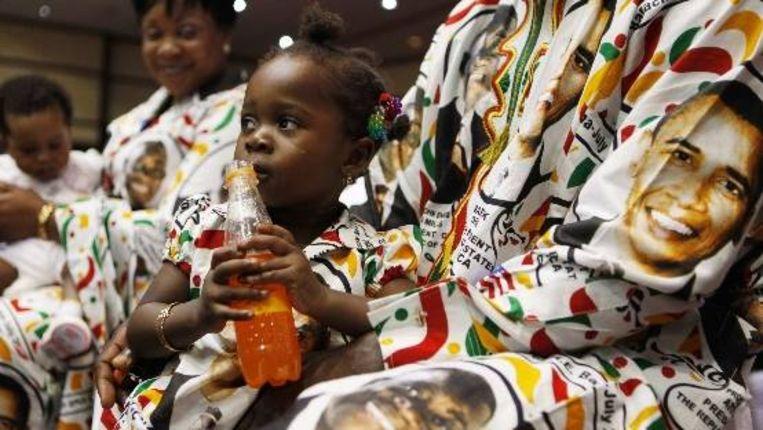 Toeschouwers gehuld in kleding waar de Ghanese en Amerikaanse presidenten op staan afgebeeld wachten op de toespraak van Obama. (AP) Beeld