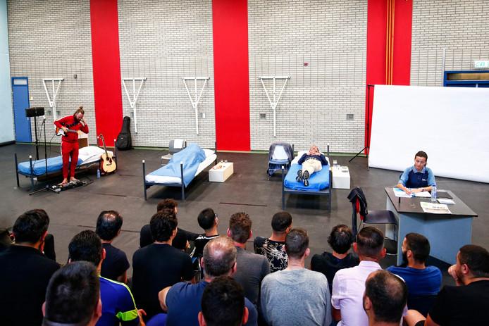 Gevangenen en bewaarders kijken naar de voorstelling Gevangenis Monologen in de gymzaal van de Penitentiaire Inrichting Nieuwegein.