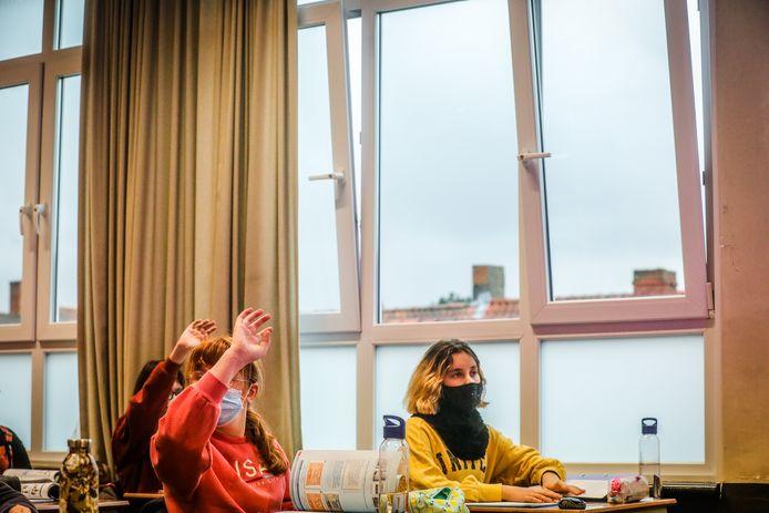 Leerlingen in de Middenschool volgen les terwijl de ramen openstaan omwille van covid.
