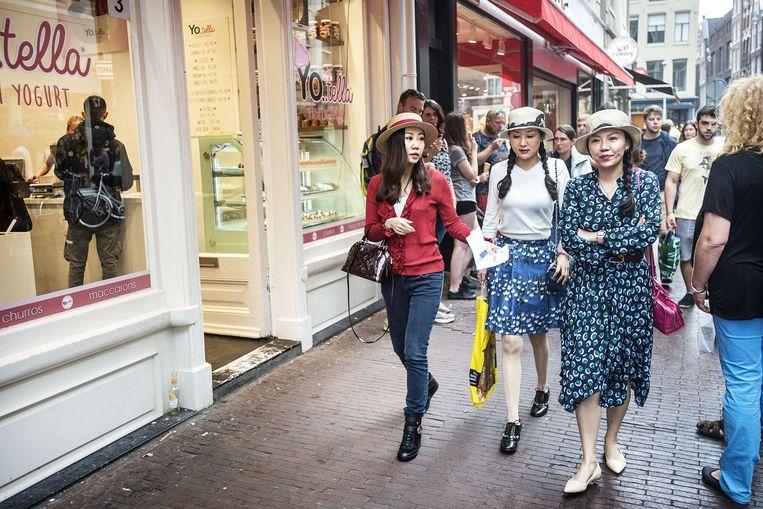 Toeristen lopen langs een ijssalon in Amsterdam. Beeld Guus Dubbelman / de Volkskrant