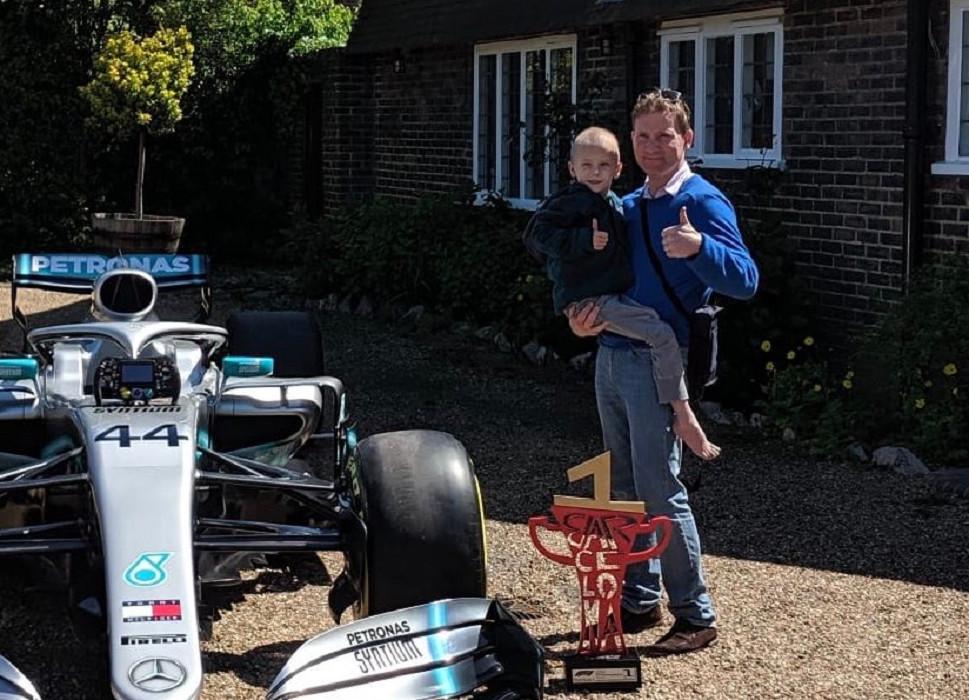 Harry en vader James poseren met de Mercedes-wagen en de door Hamilton in Barcelona gewonnen beker.