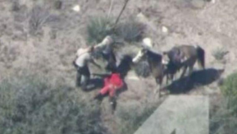 Op de grond in het rood de verdachte naast het gestolen paard, de twee agenten bij hem schoppen hem. Beeld Screenshot NBC