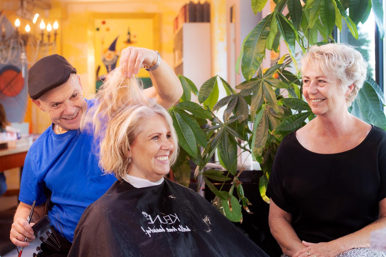 Janet kijkt toe hoe kapper Theo Anneke knipt, de zus van Henk.