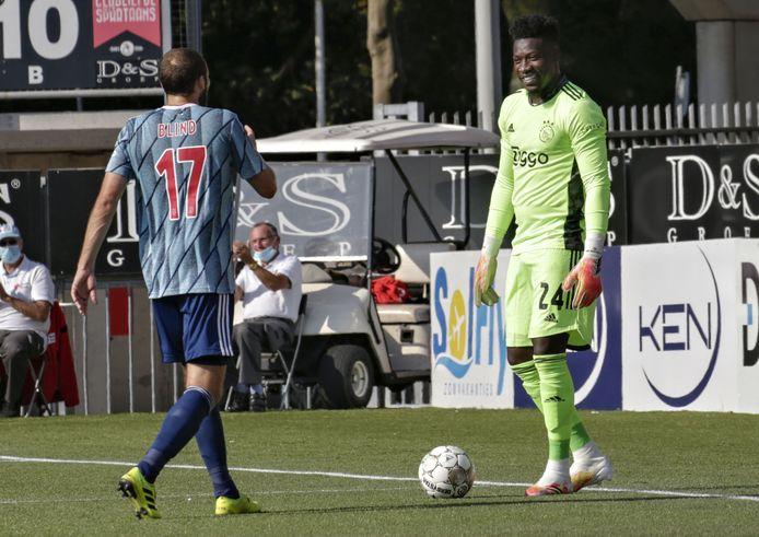 Scheidsrechter Jochem Kamphuis geeft keeper Andre Onana een gele kaart wegens (langdurig) tijdrekken. Daley Blind gaat daar even over in gesprek.