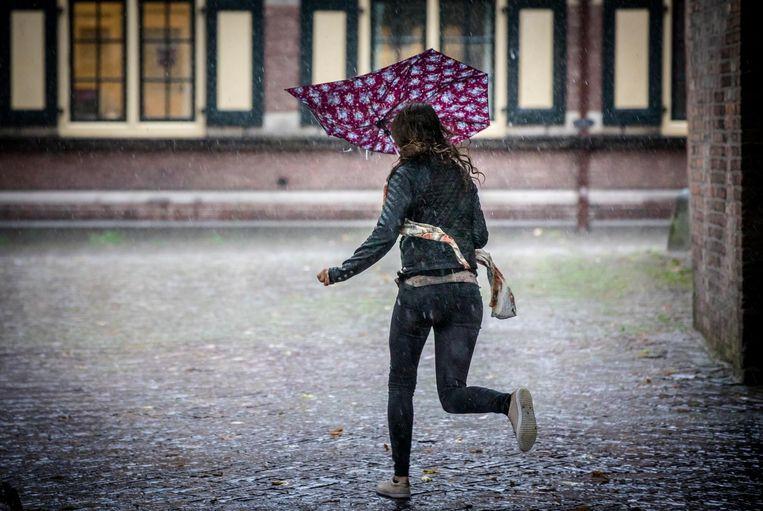 Een vrouw rent door de stromende regen over het Binnenhof. Beeld ANP