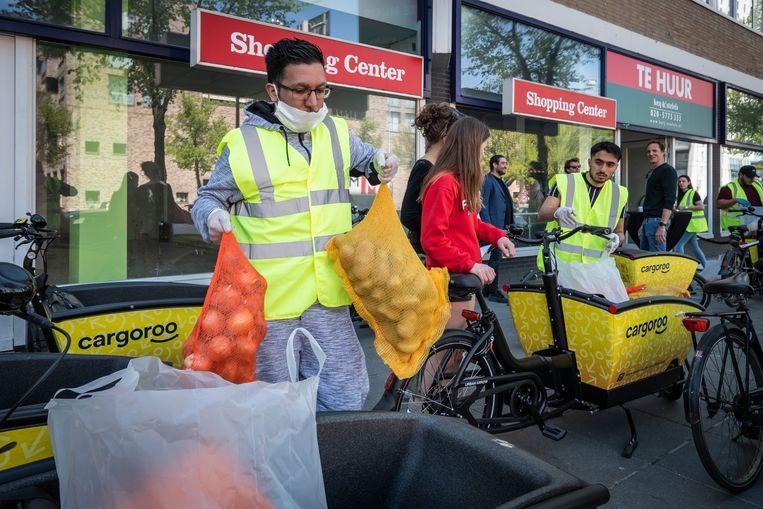 Vrijwilligers brengen de voedselpakketten weg, per auto, busje of bakfiets, naar mensen die het nodig hebben. Beeld Dingena Mol