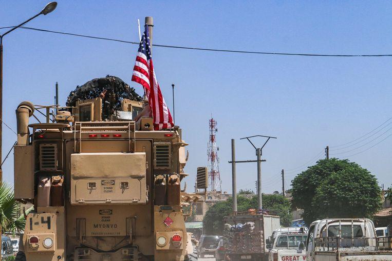 Gewapende voertuigen van de door de VS geleide coalitie rijden Ras al-Ain in Syrië in.  Beeld AFP